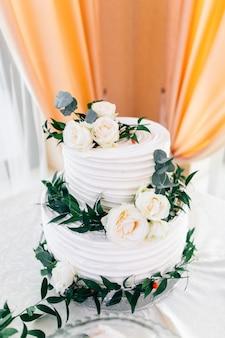 Красивый белый свадебный торт украшенный цветами