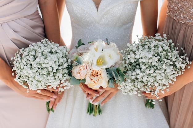 花嫁とブライドメイドの手にウェディングブーケ。カスミソウと牡丹のバラ