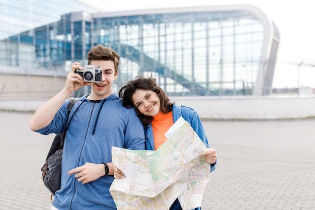 若いかわいいカップル。少年と少女が手に地図とカメラを持って街を歩いています。若者が旅行します。
