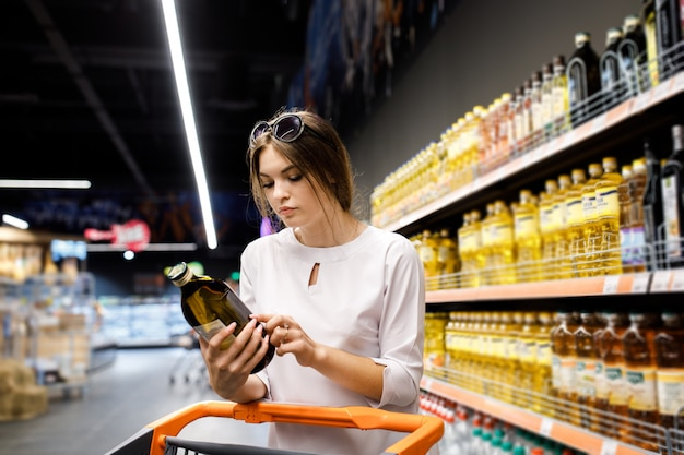 若いきれいな女の子は、大きな店で買い物をしています。女の子はスーパーマーケットで食料品を購入します。