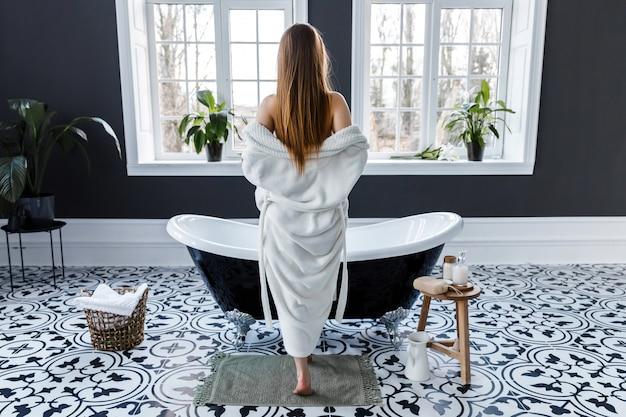 大きな窓のある美しい明るいバスルーム。若い女性はお風呂に立っている間彼女の白いローブを削除します