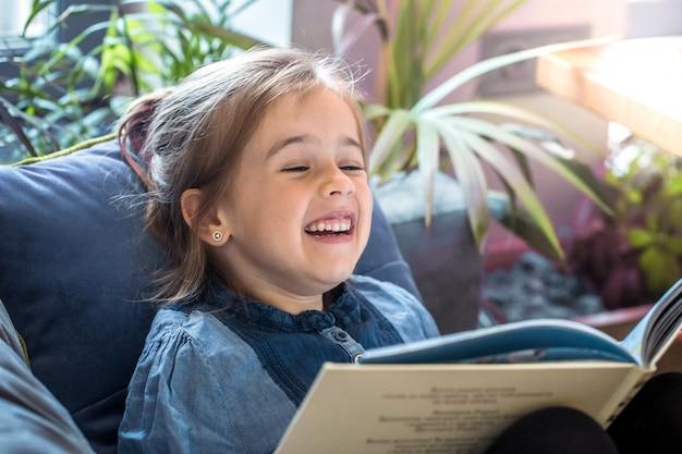 Маленькая девочка читает книгу в гостиной на диване