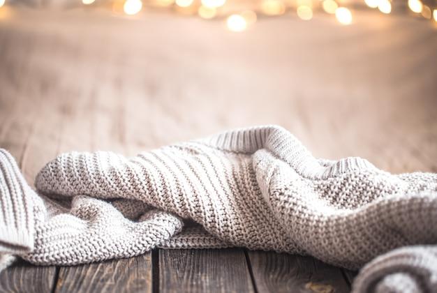 ライトとセーターが付いているお祝いクリスマス居心地の良い壁