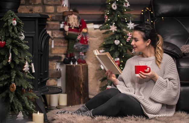 暖炉のそばの居心地の良い家庭的な雰囲気で本を読んでいる女の子
