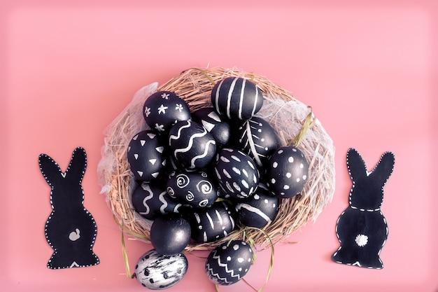 ピンクのテーブルに卵とイースターのウサギとイースター組成