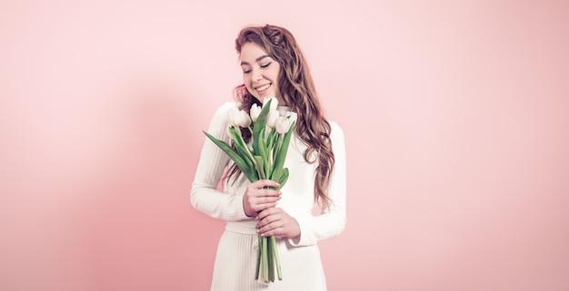 Молодая девушка с тюльпанами на цветной стене