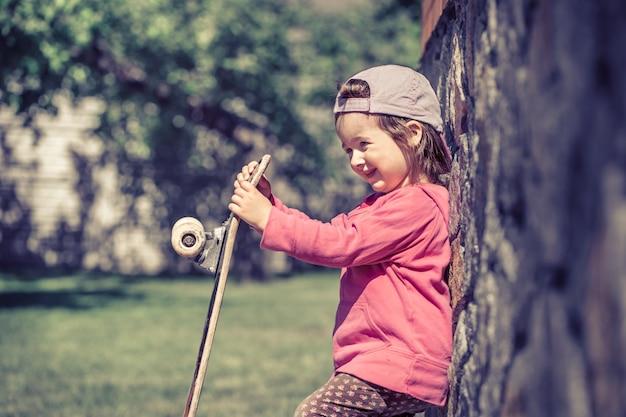Модная маленькая девочка держит скейтборд и играет на улице, красивые эмоции ребенка.