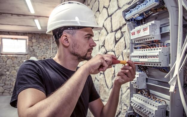 男性の電気技師は、電気接続ケーブルを使用して配電盤で作業します