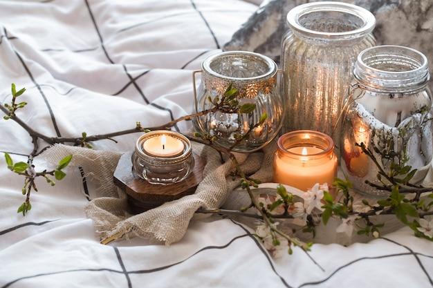 ベッドの中で異なるキャンドルのある居心地の良い静物