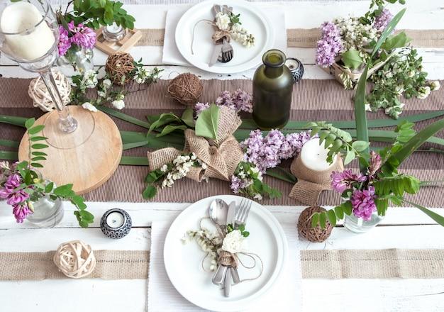 休日のための美しいエレガントな装飾が施されたテーブル-モダンなカトラリー、弓、ガラス、キャンドル、ギフトのある結婚式またはバレンタインの日