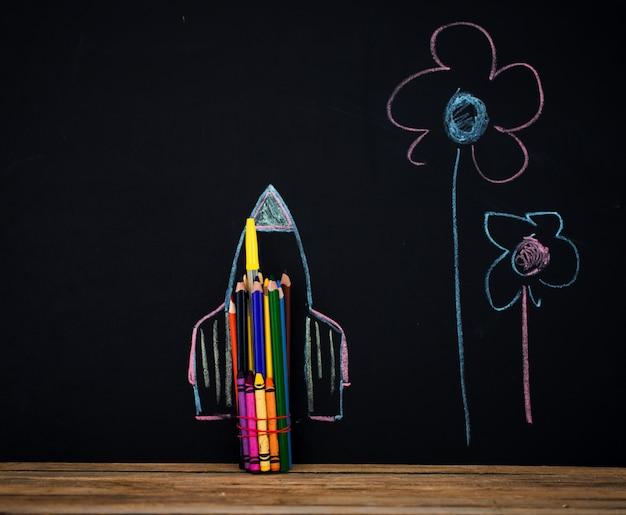 学校に戻る黒の背景、鉛筆で作られたミサイル、クレヨンの本を描く