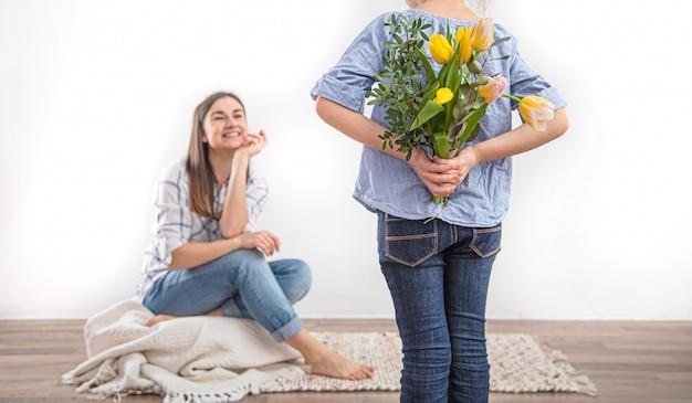 母の日、小さな娘が母親にチューリップの花束を贈ります。
