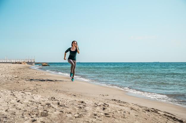 海に沿って実行しているスポーツウェアの女の子