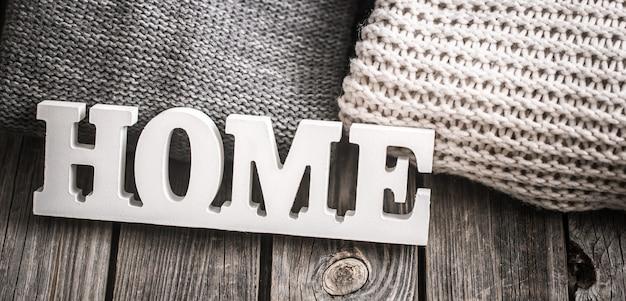 Деревянные буквы с надписью дома и вязаные свитера