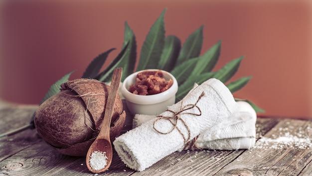 花とタオルを備えたスパとウェルネス。熱帯の花と茶色のテーブルに明るい組成物。ココナッツのデイスパ自然製品