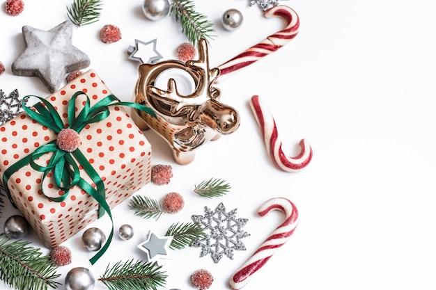 クリスマスの組成物。ギフト、モミの木の枝、白い壁に赤い装飾。冬、新年のコンセプトです。フラットレイアウト、等尺性、テキスト用のスペース