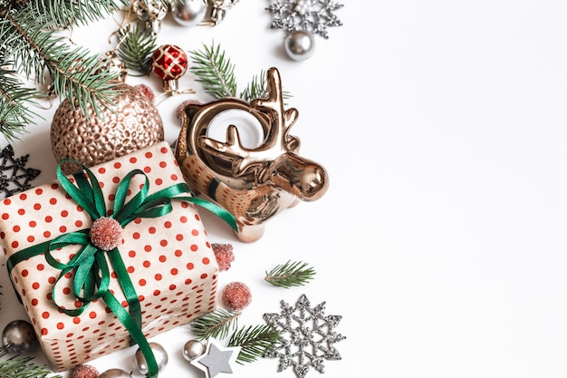 Рождественская композиция. подарки, еловые ветки, красные украшения на белой стене. зима, новогодняя концепция. плоская планировка, изометрия, место для текста