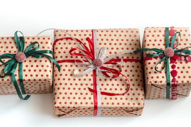 クラフトペーパーで包まれ、サテンのリボンで飾られたさまざまなギフトボックスのクリスマス組成物。平面図、フラットレイアウト。