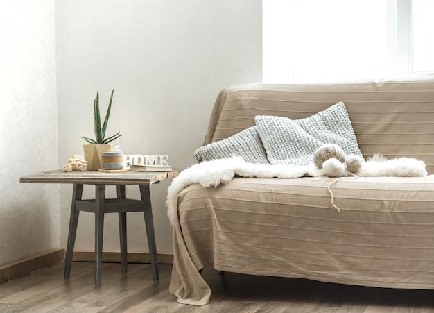 Домашний диван с предметами уютного декора в гостиной