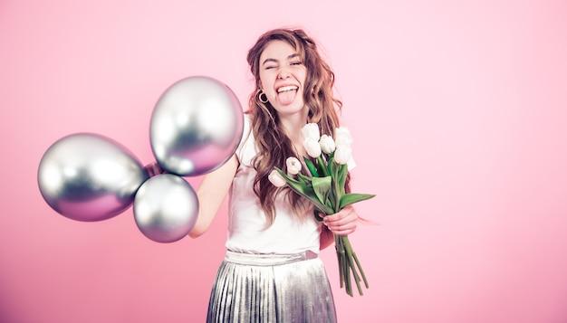 Девушка с цветами и шарами на цветной стене