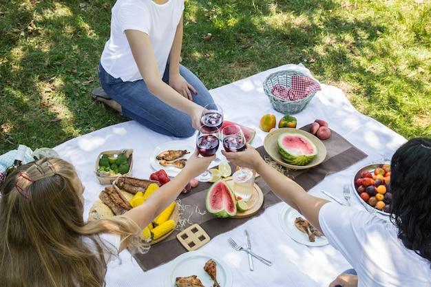 食べ物や飲み物と自然の中で友達と夏のピクニック。