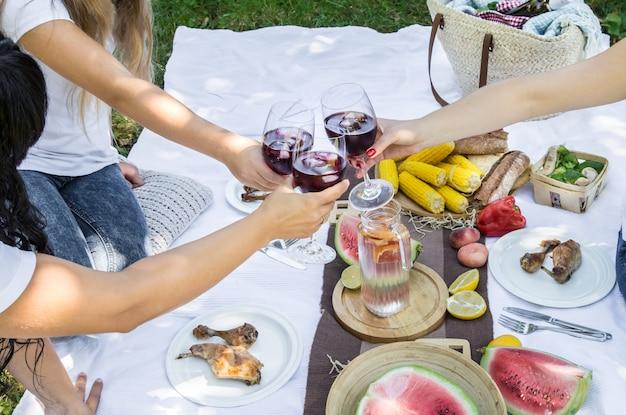 Летний пикник с друзьями на природе с едой и напитками.
