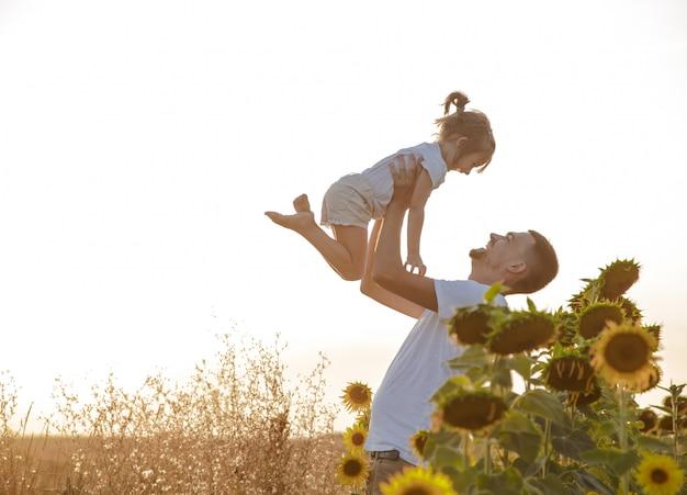 Счастливая семья, отец и дочь играют в поле