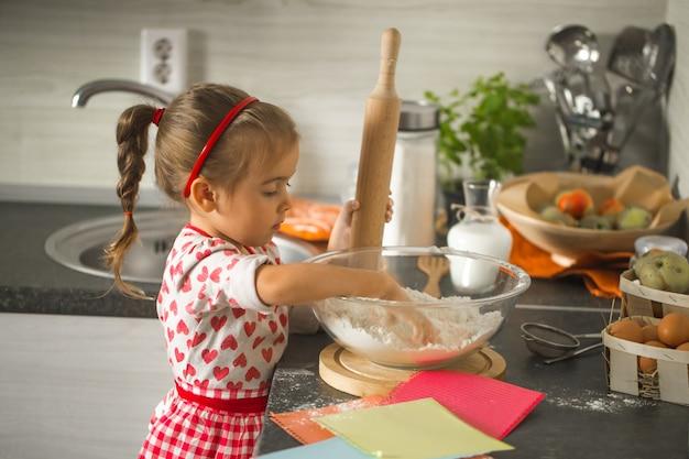 Красивая маленькая девочка бейкер на кухне