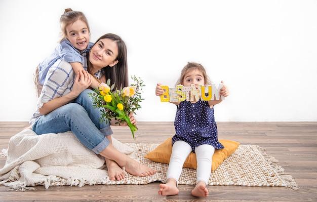 Две сестренки поздравляют маму