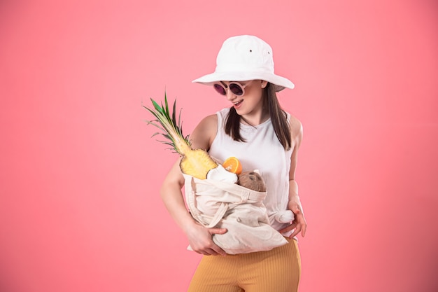 エコフルーツバッグを持つスタイリッシュな若い女性の肖像画