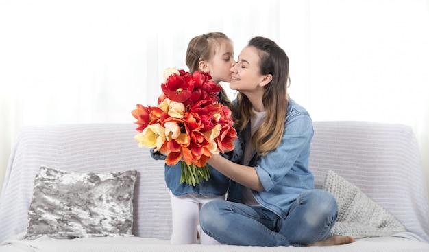 母の日。花を持つ小さな娘は母親を祝福します