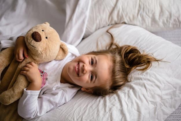 柔らかいおもちゃが付いているベッドの小さな女の子は子供の感情