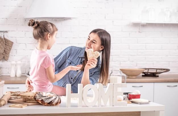 Мама и дочь готовят выпечку на кухне.