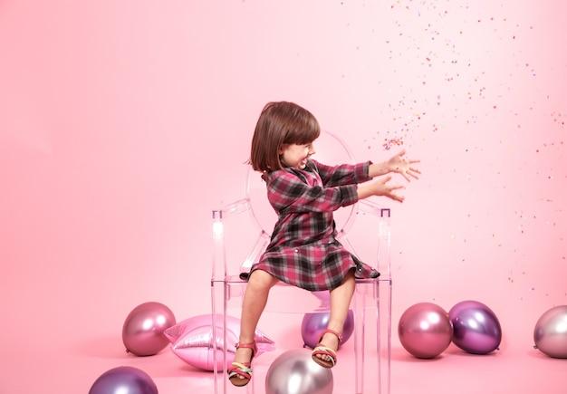 Маленькая девочка с удовольствием с конфетти. концепция праздника и веселья.