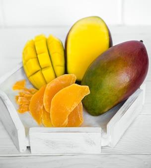ジュースと白い木製の背景にマンゴー