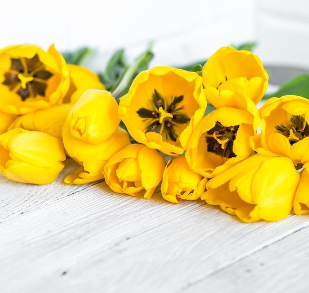 明るい木製の背景に黄色のチューリップの花束