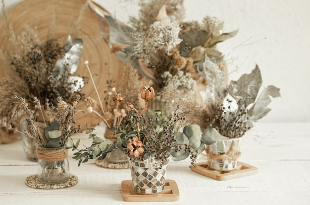 Композиция с множеством сухих цветов в вазах.
