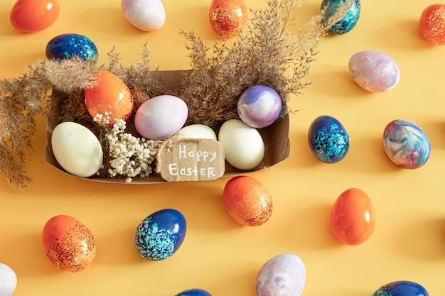 Корзина с пасхальными яйцами на цветном фоне изолированные.