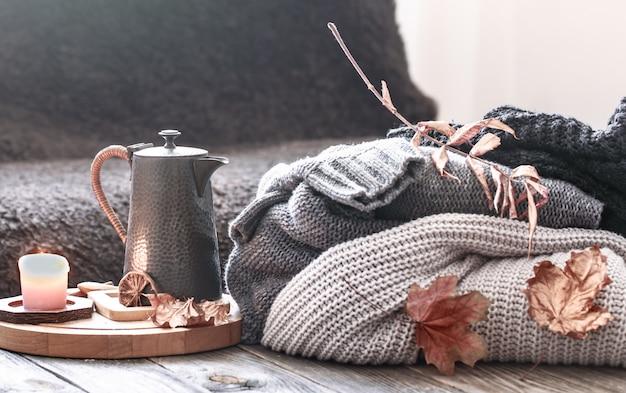 ベッドのある静物シーンで居心地の良い秋の朝の朝食。ホットコーヒーのカップを蒸し、窓の近くに立っているお茶。秋。