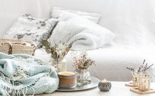 Предметы интерьера в интерьере. бирюзовое одеяло и плетеная корзина с вазой цветов и свечей