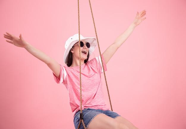 Молодая женщина на качелях на розовом фоне.