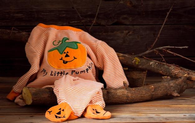 木製の背景上の子供のためのハロウィーンの衣装