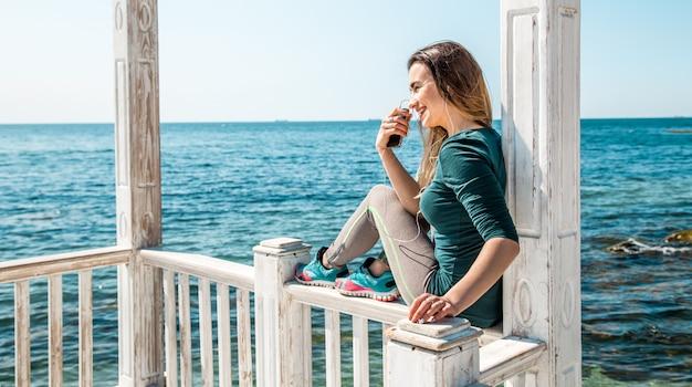 電話で桟橋にスポーティな女の子