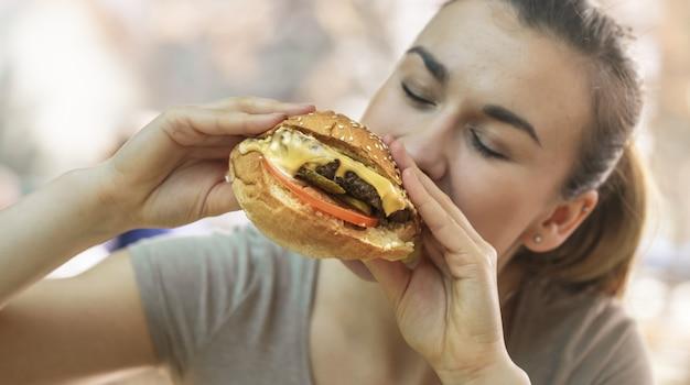 Молодая женщина в кафе ест вкусный бутерброд