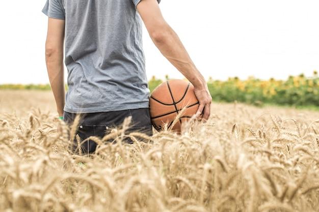 Молодой человек с баскетбольным мячом на природе, концепция спорта