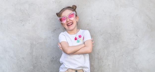 Веселые маленькие девочки на сером фоне текстурированных. открытый портрет маленькая девочка. серый текстурированный фон стены.