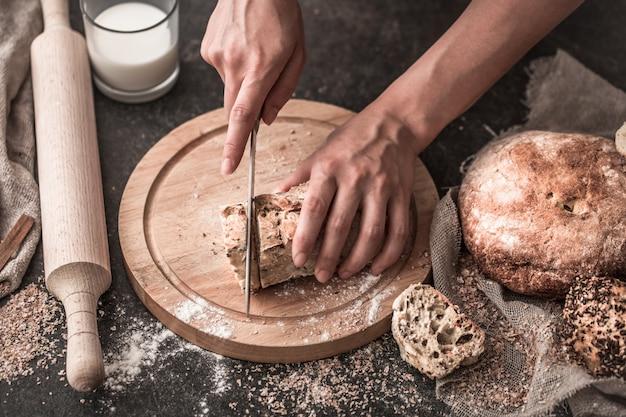Свежий хлеб в руках крупным планом на старых деревянных фоне