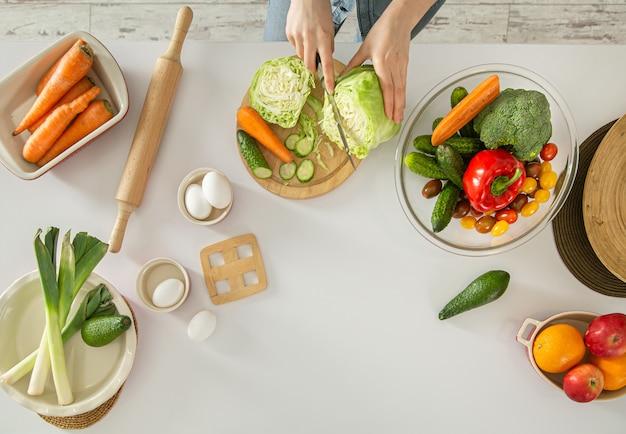 若い女性は台所でサラダを準備しています。