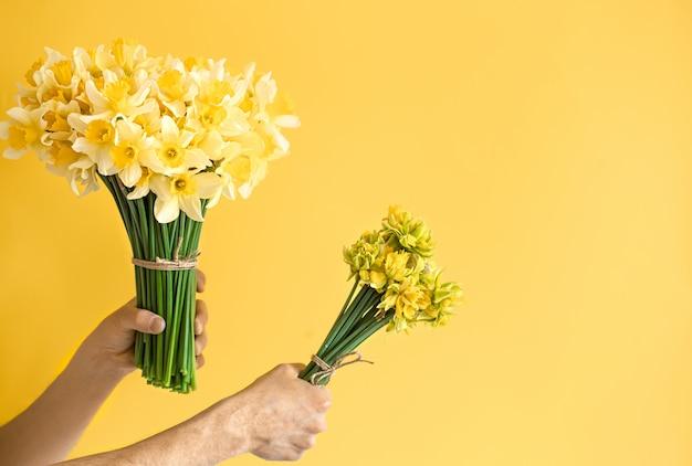 花の花束と背景の男性の手。