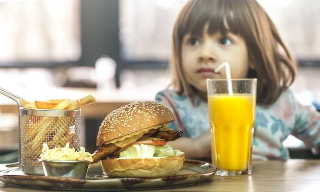 小さな女の子がファーストフードカフェで食べる